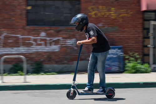 Man riding the Unagi Model One electric scooter