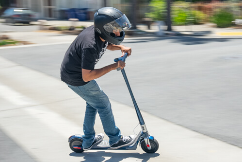 Man leaning hard into turn on Unagi Model One electric scooter