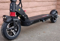 Lower half of an electric scooter showing tires and brakes