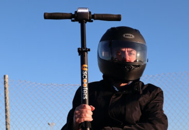 Man wearing helmet and holding electric scooter