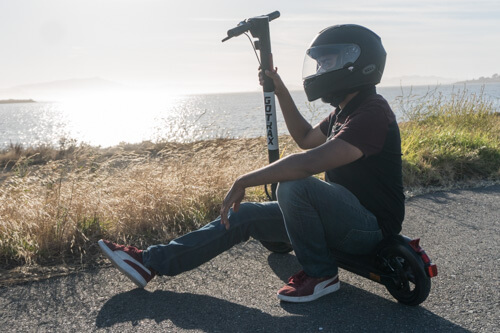 Man crouched next to the Xr Elite electric scooter