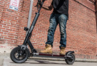 Man accelerating on the EVOLV Tour XL Plus electric scooter