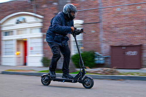 Apollo Ghost electric scooter - man riding scooter to left of frame, going fast, full view