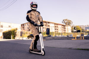 Segway Ninebot Air T15 electric scooter - man riding scooter to right, full view