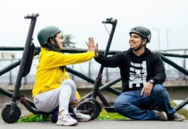 2 people high five while sitting on scooters