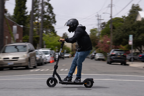 Apollo Air electric scooter - man riding scooter through intersection, to left, side view