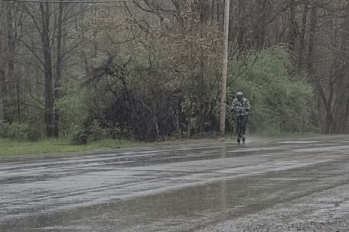 Alex Simon riding electric scooter in the rain, long shot